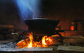 Cooking pot over smoking, indoor open flame cookstove.