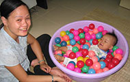 Baby lies in purple bucket full of balls, woman seated cross-legged on floor