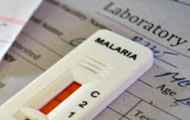 close up of white malaria test showing red indicator sitting on top of sheet of paper with title laboratory