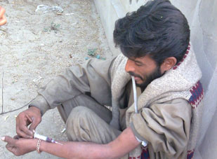 Pakistani man squats on ground against wall while injecting needle into forearm
