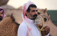 Man stands and strokes camel's neck