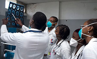 Group of medical trainees in Maputo Central Hospital, Mozambique gathers around a trainer to review x-ray held up to the light