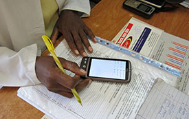 Photo courtesy of Dr. Marc Mitchell. Worker in clinic enters data from paper using a mobile device.