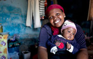 Photo by James Pursey, Elizabeth Glaser Pediatric AIDS Foundation, Young woman smiling at camera holds young baby