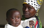 Mother wearing bright shall and head wrap over hear holds an infant in her arms, both look at camera