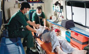 Two medical workers in an organized ambulance work with an injured patient reclined on a mobile stretcher