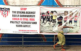 Woman walking in street in Monrovia, Liberia, in front of large football banner reading: stop the stigma against Ebola survivors. © 2016 Sean G. Smith / Critical-Care Professionals International, Courtesy of Photoshare.