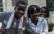 Three teenagers laugh and smile in an outdoor courtyard in Haiti, one holds a smartphone