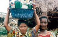 Two African women outdoors, one balances tub full of alcohol bottles on her head