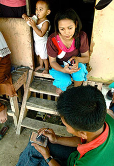 Photo courtesy of DataDyne.org, man seated enters data on a handheld device, woman faces him sitting on wooden steps in doorway