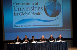 Row of 6 men seated at a panel table at the front of a conference room under a projected slide reading Consortium of Universities for Global Health