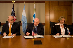 PHOTO: Seated at a long table Argentine Ambassador Héctor Timerman watches as NCI Director Dr. John E. Niederhuber and Urugayan Minister of Public Health Dr. Mária Julia Muñoz, sign papers.