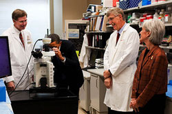 PHOTO: President Obama look into a microscope in a laboratory at NIH, while Dr. Marston Linehan, NIH Director Dr. Francis Collins and HHS Secretary Kathleen Sebelius look on.